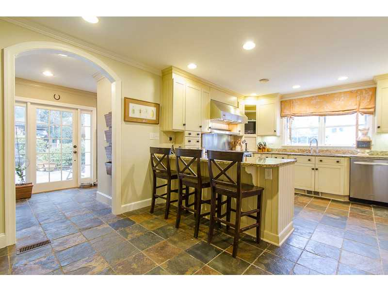 Kitchen. Spacious kitchen with slate floor open to mudrrom, laundry room, and office with door leading to patio