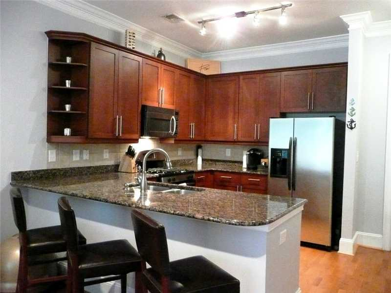 Kitchen. Kitchen features cherry cabinets, breakfast bar, Baltic Brown granite counters, stainless s