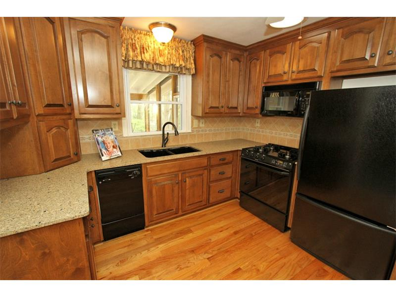 Kitchen With Granite Counters and Wood Cabinets. Gas Stove. Window overlooks Back Yard & Deck