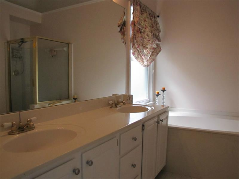Master bath has dual sinks and a garden tub with a separate shower.