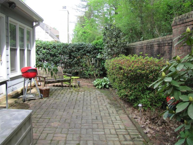 Private bricked patio with mature landscaping.