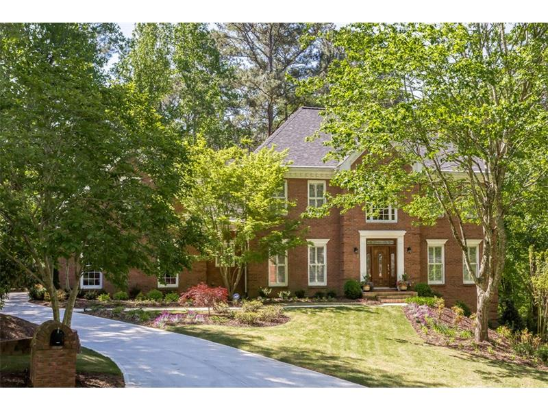 FRONT EXTERIOR: This beautiful, traditional Sandy Springs home is situated in the prestigious Grogans Bluff subdivision and boasts a four-sided brick exterior with new HardyPlank accent paneling in the rear and a two car side entry garage.