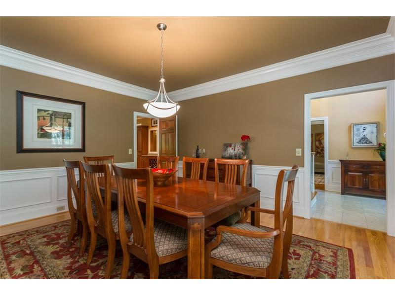 DINING ROOM: The gorgeous formal dining room is large enough to comfortably seat your next dinner party of 12 or more guests and is complete with hardwood floors, picture molding, an upgraded crown molding package and wood shutters.