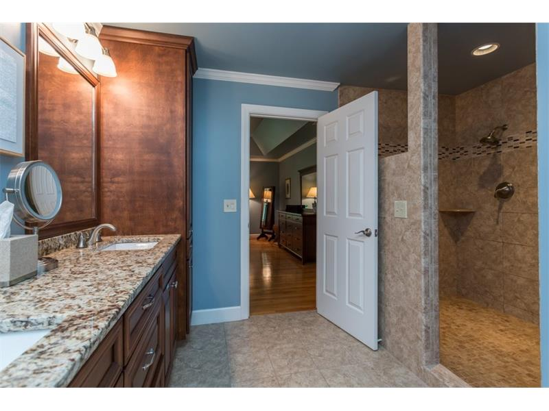MASTER SUITE: The recently renovated Master bathroom impresses with double granite vanities, beautiful stained cabinetry, a private water closet and large free standing garden tub perfect for long soaks after a stressful day.