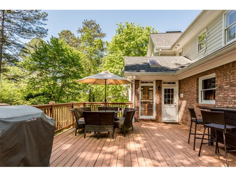 REAR EXTERIOR: The rear exterior of the home is the ideal place to entertain with a large oversized deck overlooking the backyard. Mature trees and lush greenery surrounding the yard provide a private, relaxing place to gather and socialize.