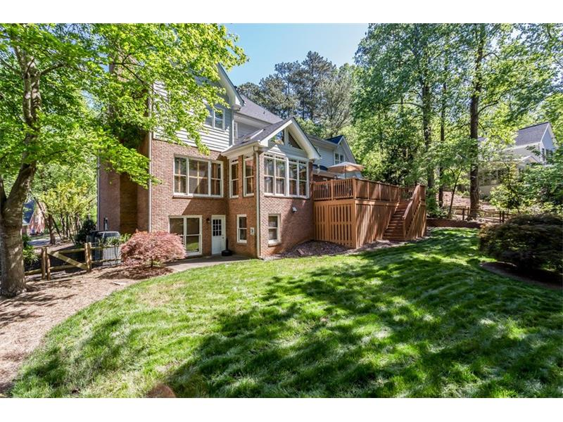 REAR EXTERIOR: A set of stairs leads you from the upper deck to the backyard, which is professionally landscaped and fenced in and includes open green space for your four-legged friends or summer games of croquet or flag football.  The back yard also