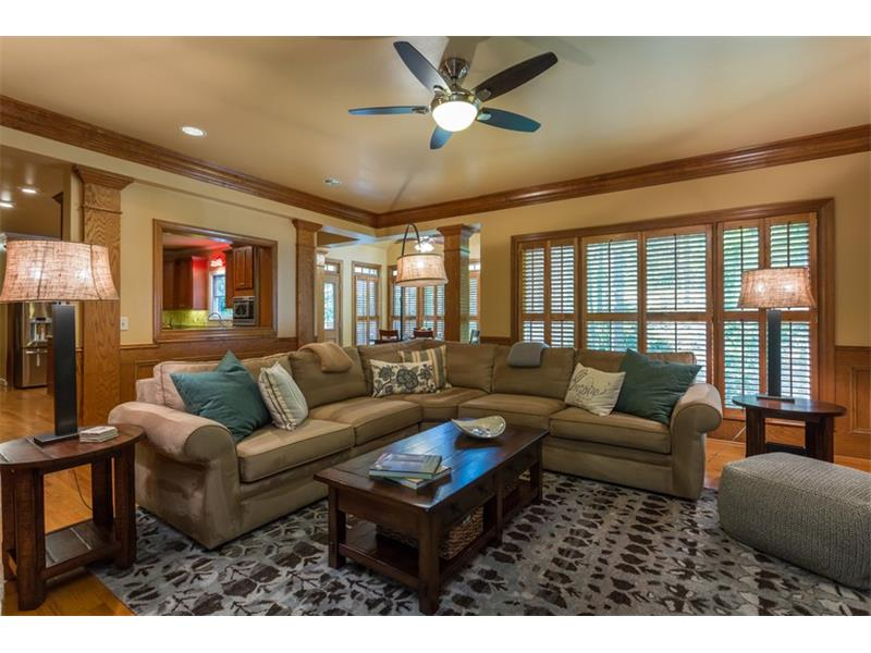 FAMILY ROOM: Features include wood paneling, a brick gas fire place with a mantle, built-in book cases and cabinetry, hardwood floors and wood shutter blinds.