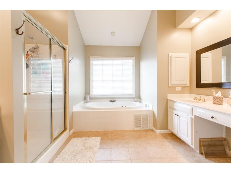 Master bath features his and hers vanity, separate deep soak tub and shower and travertine finishes.  You will love the large walk in closet.