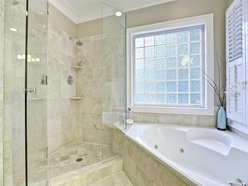 Large walk-in shower with 2 shower heads, jetted tub, heated floors, plantation shutters - this en suite bath has it all!