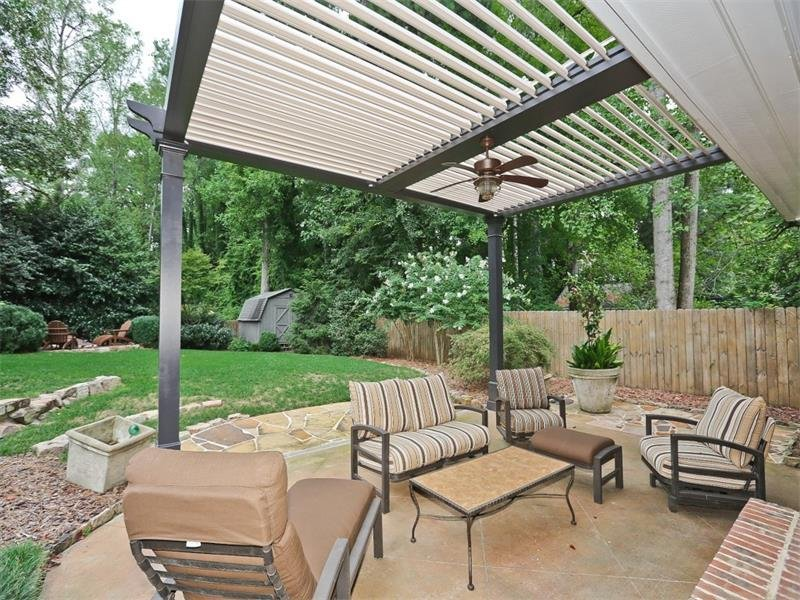 This picture shows the louvered ceilings open. Notice the in-ground firepit and shed with electricity and attic fan in the backyard.