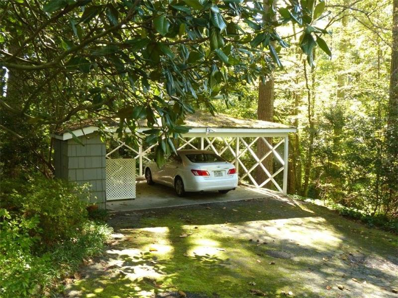 Separate carport with  side storage shed also features the original cupola on top.