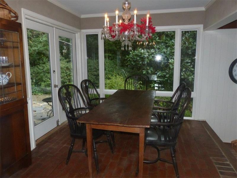 The separate dining room features brick floors and access the backyard with glass doors.