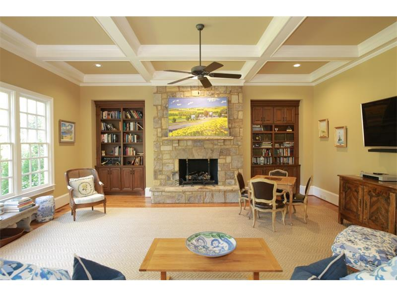 The family room with its fireplace and coffered ceiling opens to the bright and airy breakfast area and kitchen.
