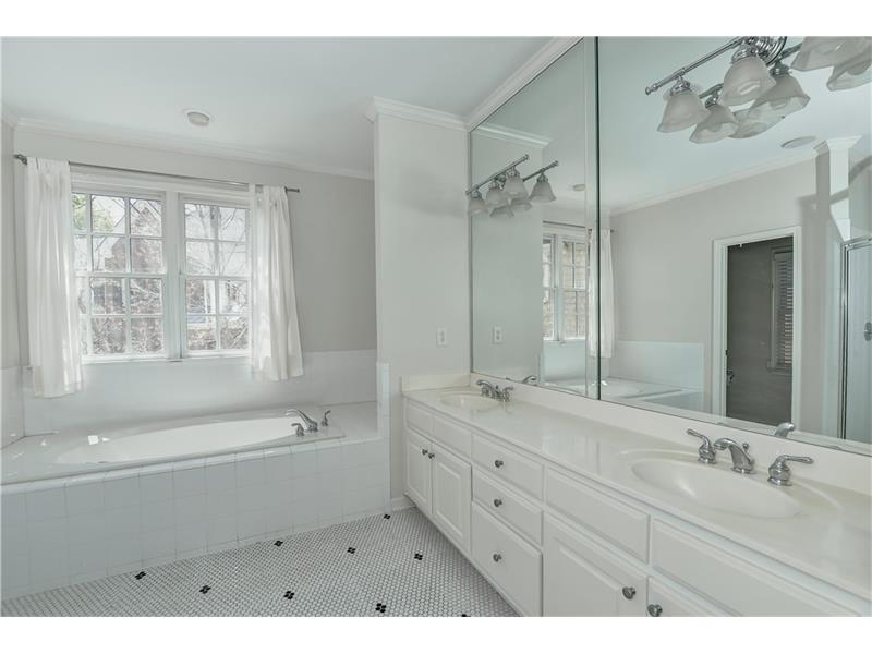 Clean and calming white Master Bath with timeless black and white penny tile, a soaking tub and a large separate shower