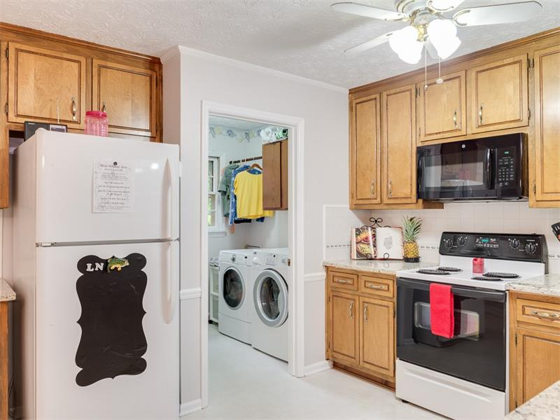 Laundry Room off the Kitchen has cabinets, 2 hanging rods and laundry sink.