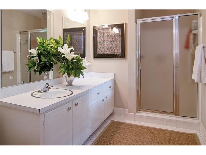 The master bath has white tile and large vanity with cabinets.