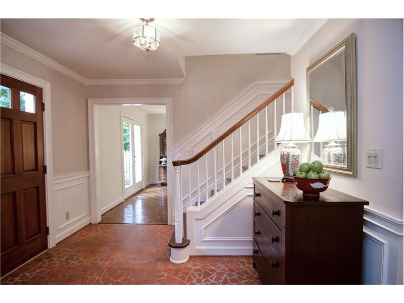 The entry foyer features chair rail and wainscoting .