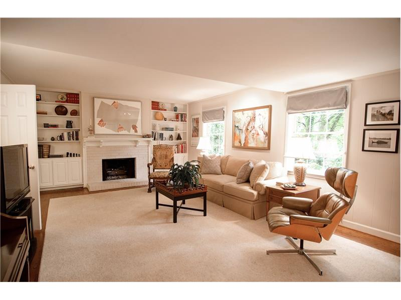 The spacious family room has a fireplace with stone surround, hardwood floors and built-ins.