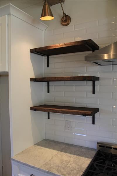 Angle iron open shelves, large format beveled subway tile and library lights.