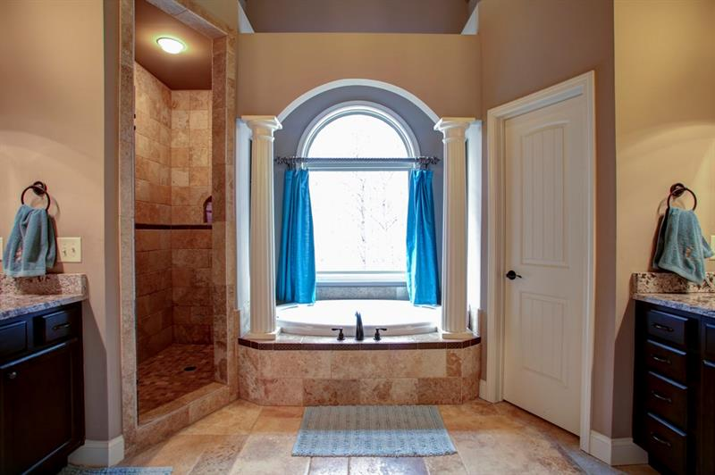 Elegant columns, arched accents & cathedral ceiling make this master bath a retreat!