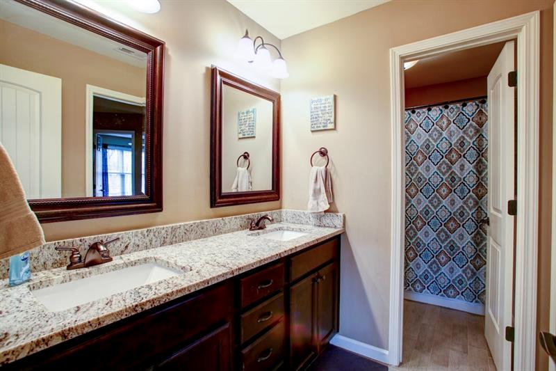 Huge double vanity in the upstairs full jack & jill bath! Tiled floors, custom cabinets, granite & light fixtures are beautiful!