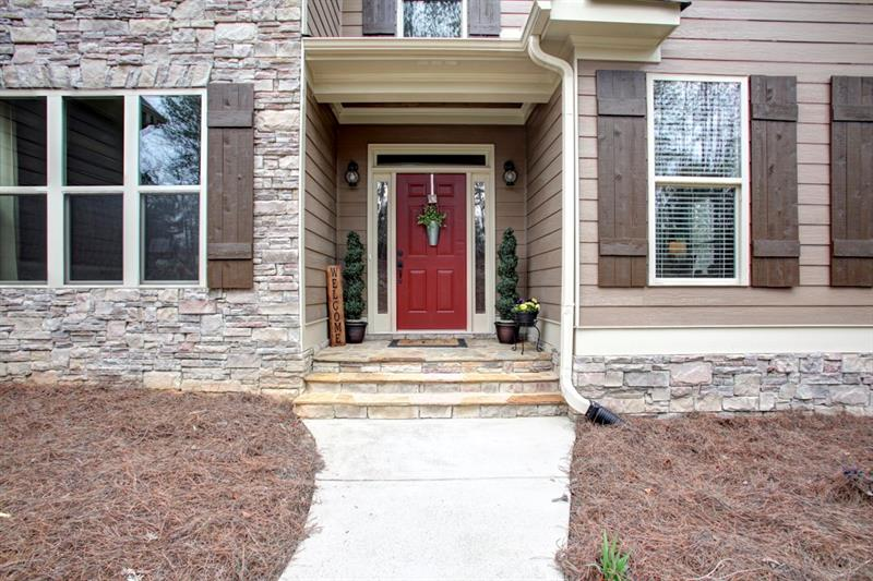 No detail left undone! Beautiful red front door accents the welcoming stacked stone front porch!