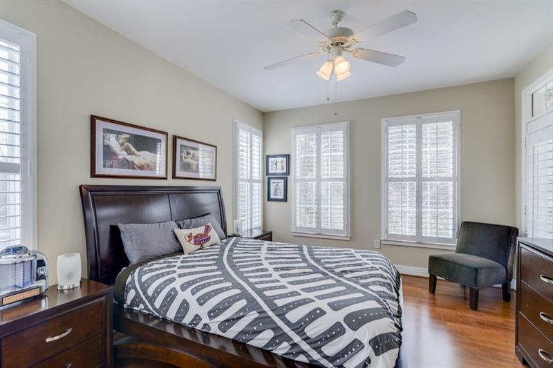 Master bedroom with new hardwood flooring, plantation shutters and door to the balcony. Corner unit=abundant natural light.