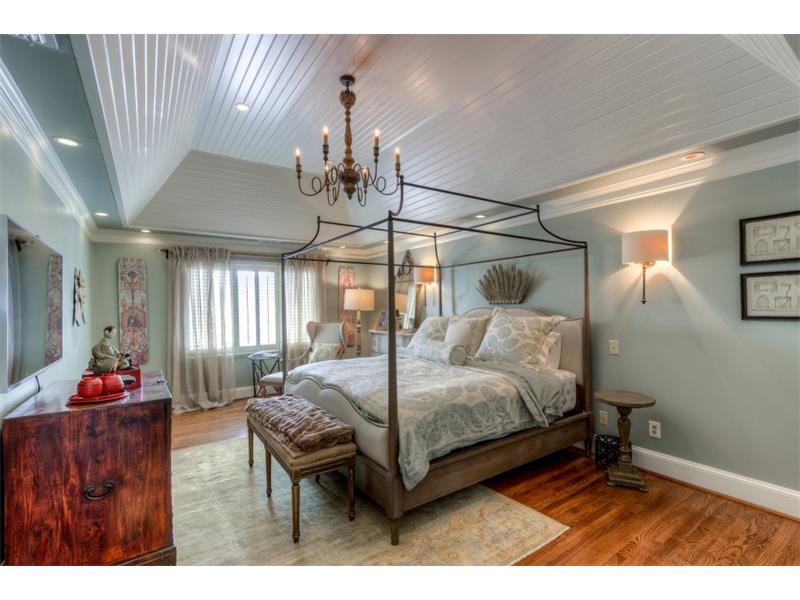 Master bedroom with cathedral, vaulted Tuscan tongue and groove ceiling, designer sconces and chandelier.Hardwood floors are new!