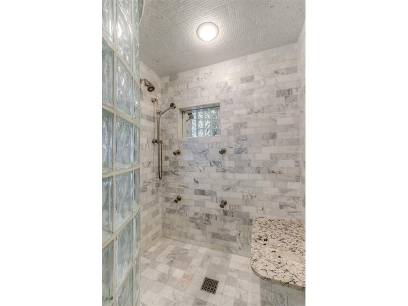 Huge shower with curved glass and multiple shower jets as well as steam