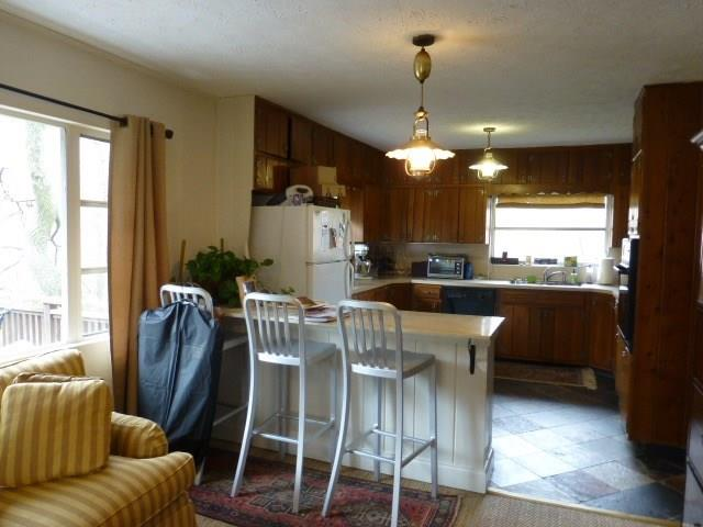Apartment has full kitchen with solid wood cabinetry and stone floors.