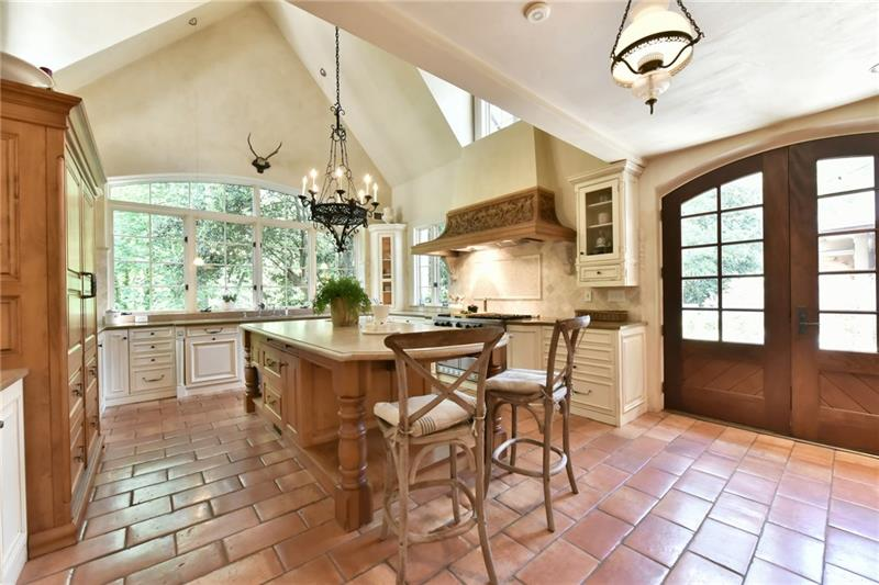 Soaring vaulted ceilings with dormer windows fill this kitchen with light ! A wall of windows overlooking the 1.6 acre private estate lot. Double solid mahogany doors lead to one of the stone loggias.
