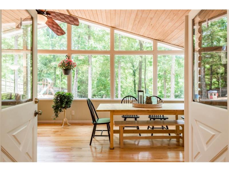 Spacious sunroom looks out to private tree lined yard