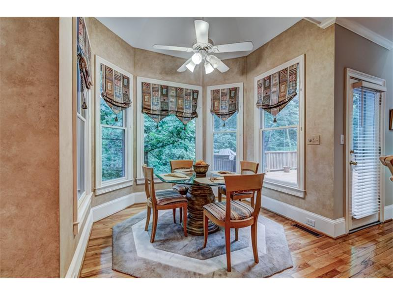 Pretty breakfast area is surrounded by windows that look out over the deck and private, wooded back yard