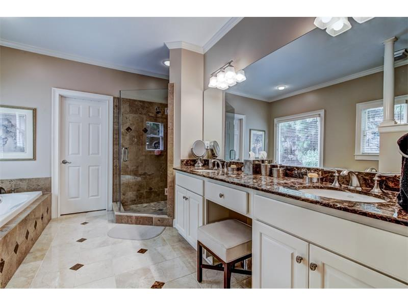 The bathroom features a double vanity, toilet closet, whirlpool tub and separate glass door shower.