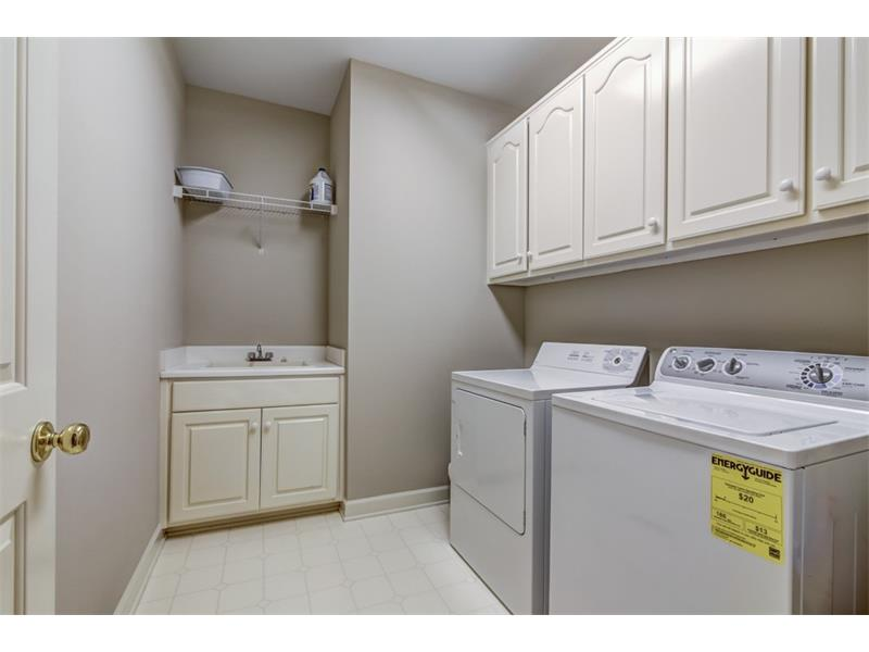 Full laundry room with cabinets and wash sink on the main level of the home