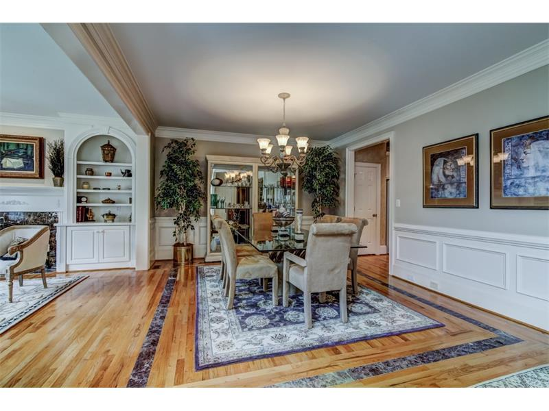 The formal dining room is defined by inlaid marble tile in the hardwood floors as well as elegant wainscoting.