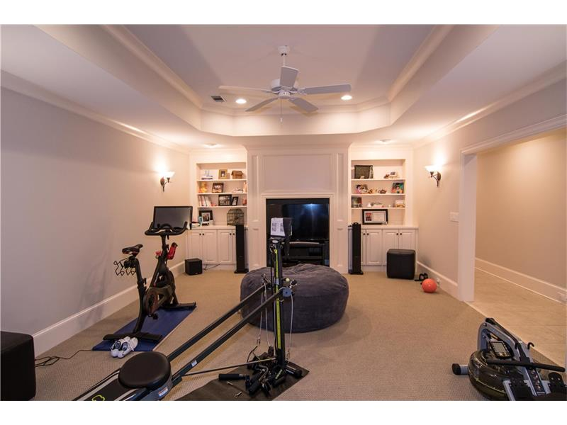 Large basement family room with built-ins. Tray ceiling, sconces and wired for sound. (used as a workout room)
