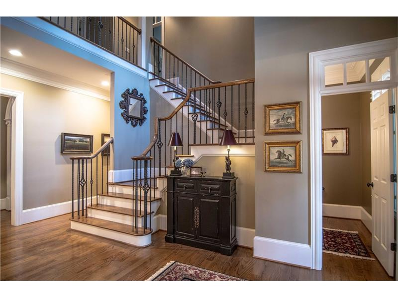 One of two main floor powder rooms off foyer. Grand staircase to upper level. Foyer leads to dining room, great room and main hall.