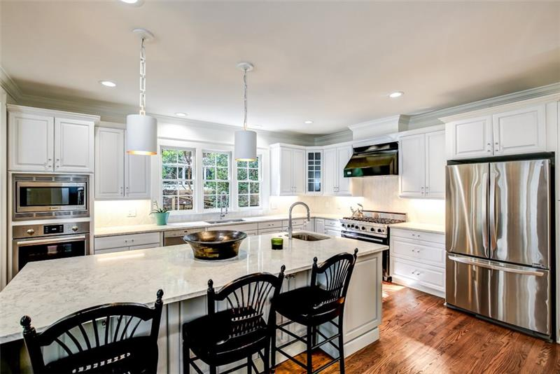 Renovated Kitchen with white cabinetry, stone countertops, Wolf range, and island with breakfast bar
